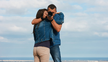 Beautiful young couple hugging, holding camera