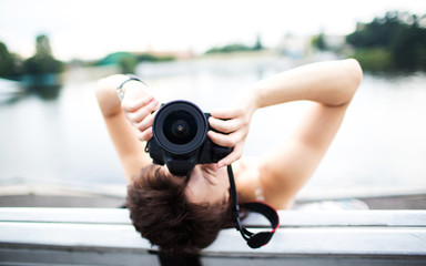 Portrait of a photographer covering her face with the camera..