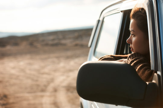 Woman looking out the window of her car