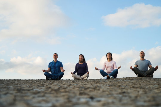 Group of four people practicing meditation and yoga
