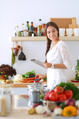 Young woman using a tablet computer to cook in her kitchen . Young woman