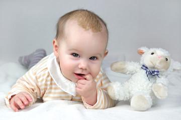 Drei Monate altes glückliches Baby mit Milchschorf liegt mit Plüschtier auf der Decke