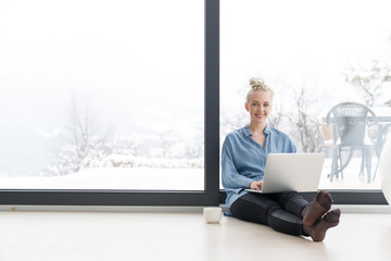 woman drinking coffee and using laptop at home