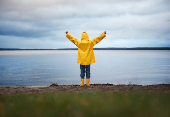 Little Boy in Yellow Rain Coat raising his arms in front of an autumn Lake: He his ready to take on the world and any adventure that comes his way