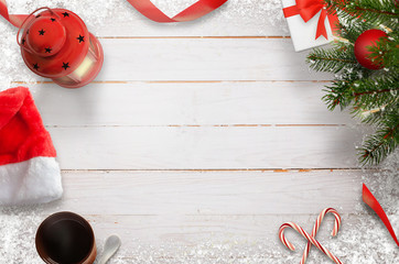 Christmas composition of Christmas tree, decorations, lights; snowflakes; gift, lantern, lollipop, tea, hat on wooden white table. Top view.