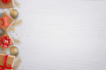 Christmas background with gifts and fir tree branches on left side. Blank space for greeting text. Top view of white wooden table.