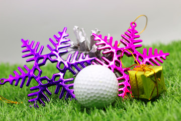Golf ball with Christmas decoration on green grass