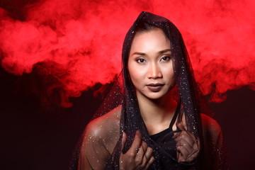 Smoke Tan Skin Asian Woman black hair dark lip with Dense Fluffy Puffs of White Smoke and Fog on dark Background