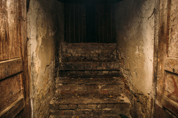 Dirty grunge creepy wooden staircase from abandoned basement, place where homeless people live, exit to dark street