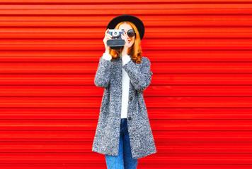 Fashion portrait pretty woman with retro camera on a red background
