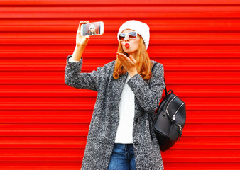 Fashion pretty cool young girl takes a picture self portrait on a smartphone on a red background