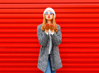 Fashion pretty woman blowing red lips sends an air kiss on a background