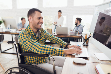 A man in a wheelchair is working the computer at a table in a modern office.