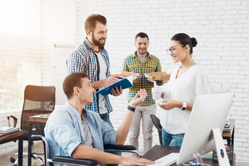 Office workers and man in a wheelchair are eating pizza. They work in a bright and modern office.