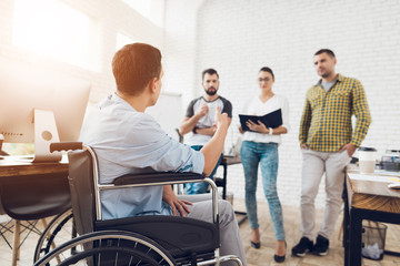 A man in a wheelchair is showing documents to his team in office. The are working in a bright modern office.