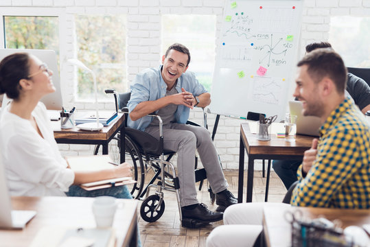 Office workers and man in a wheelchair discussing business moments in a modern office.