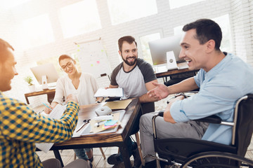 A man in a wheelchair communicates cheerfully with employees of the office during a business meeting.