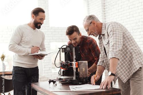 Three men set up a self-made 3d printer  One of the men checks the