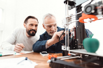 Two engineers print the details on the 3d printer. An elderly man controls the process.