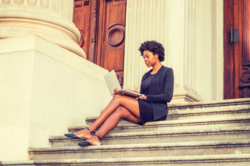 African American female college student with short afro hairstyle studies in New York, wearing fashionable work clothes, sits on stairs outside office on campus, reads, works on laptop computer..