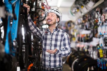 friendly man in helmet chooses for himself sports bike in bicycle shop