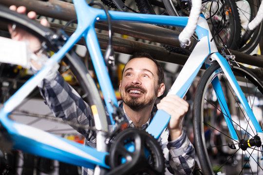 man checks bicycle frame in shop when choosing bike