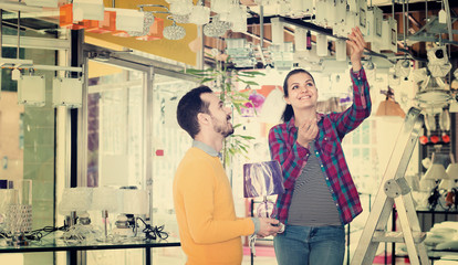Smiling man and girl in lighter shop choosing stylish pendant lamp