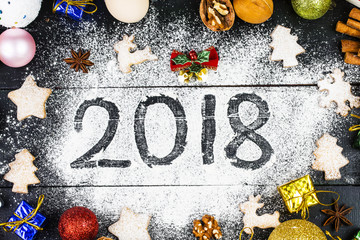 Happy New Year 2018 written on flour and Christmas Decorations Gingerbread cookies, cinnamon, oranges, spices, nuts and cookie cutters on wooden background. Christmas card, New Year greeting card