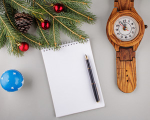 Empty sheet of paper, pen, a spruce branch and Christmas-tree toys on a light gray background. With copy space. Business desk table concept.