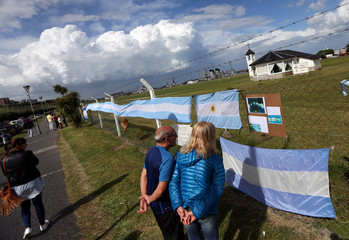 People look at signs in support of the missing crew members of the ARA San Juan submarine in Mar del Plata