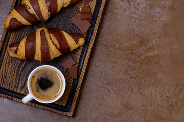 Closeup coffee and chocolate croissant and chocolatier