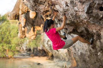 Young woman rock climber climbing on seaside cliff