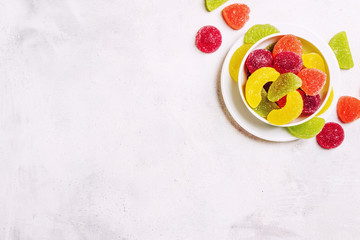 Multicolored jelly marmalade in sugar, gray background, top view