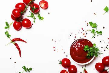 Fototapeta Tomato ketchup sauce with spices and herbs with cherry tomatoes in a bowl on white food background, top view obraz