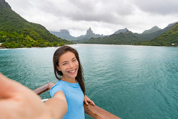 Cruise travel luxury vacation in Bora Bora Asian woman tourist taking selfie picture with phone on deck of cruising ship with French Polynesia landscape background. Happy girl holding smartphone.