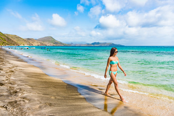 Caribbean travel cruise tourist on St Kitts beach. Cruise ship tropical holiday. Bikini woman walking relaxing enjoying sun tan sunshine on South Frigate Bay beach in Saint Kitts.