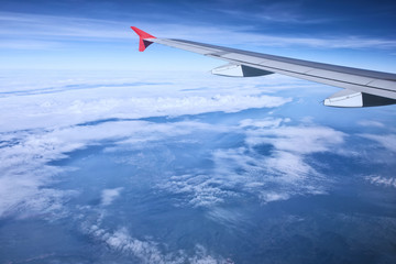 aerial view of passenger plane flying over beautiful blue sky and white cloudA