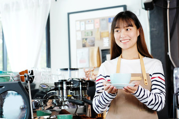 Young asia woman barista serving coffee cup with smiling face at cafe counter background, small business owner, food and drink industry concept