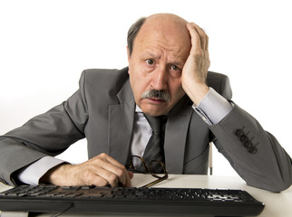 business man with bald head on his 60s working stressed and frustrated at office computer laptop desk looking tired