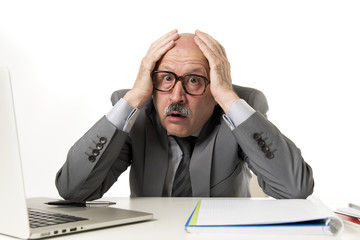 mature business man with bald head on his 60s working stressed and frustrated at office computer laptop desk looking desperate