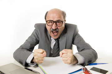 60s bald senior office boss man furious and angry gesturing upset and mad sitting on desk with paperwork in business and job problems