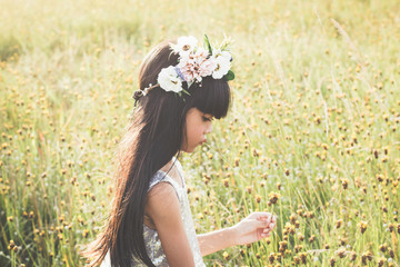 Beautiful Little girl in a field of flowers - Evening light with Retro Vintage filter