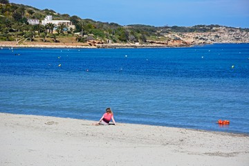 Girl sitting on the beach with the coastline to the rear, Mellieha, Malta.
