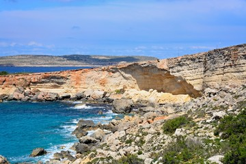 Rocky coastline with Comino to the rear, Paradise Bay, Malta.