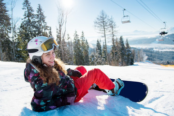 Smiling female snowboarder lying on the snow under a ski lift in the sun rays on a beautiful sunny winter day at ski resort in the mountains