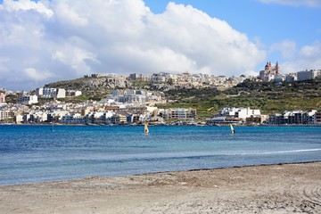 View of the sandy beach with town buildings across the bay, Mellieha, Malta.