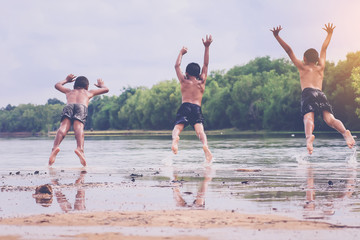 three asian young boys jumping into the lake.