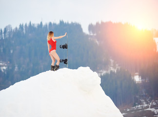 Hot woman snowboarder wearing red swimsuit, standing with snowboard on snowy slope at ski resort, enjoying beautiful sunset. Ski season and winter sports concept