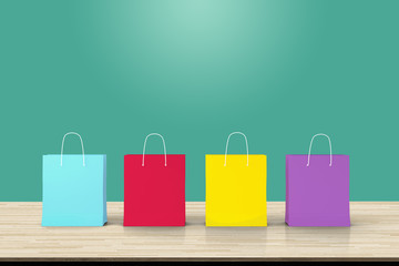 Four paper shopping bags on wood table backdrop. Concept about online shopping or E-commerce that everything can be bought easily by using an internet.