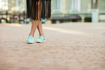 attractive young girl dancing near building in the street. slim woman in black leather skirt, close uo view of legs